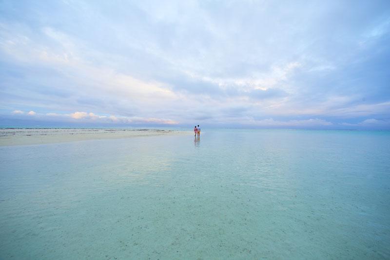 Couple walking along of Polynesian motu