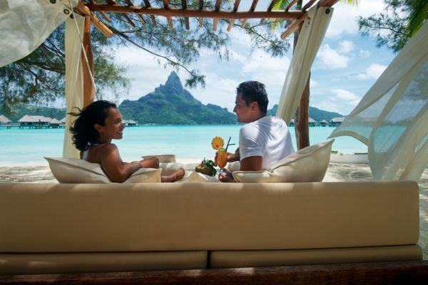 couple in front of Bora Bora island taking on the beach